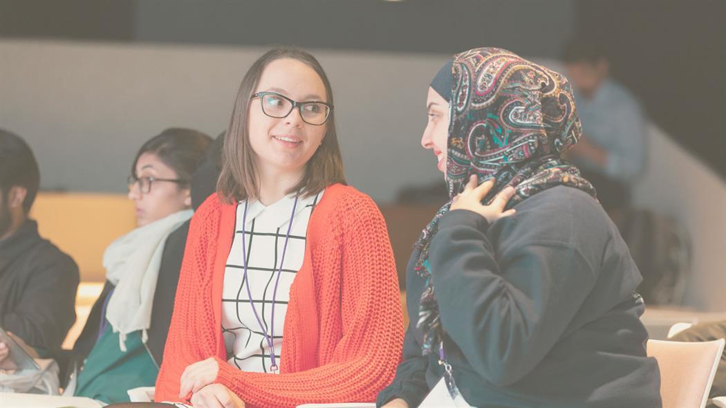 Zwei weibliche Studentinnen sitzen lächelnd nebeneinander und reden.