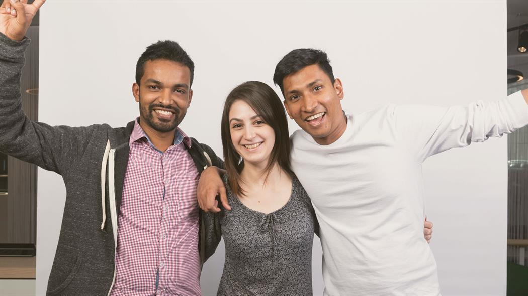 一女两男三名学生对着摄影师摆姿势。他们面带笑容,相互搭着肩。